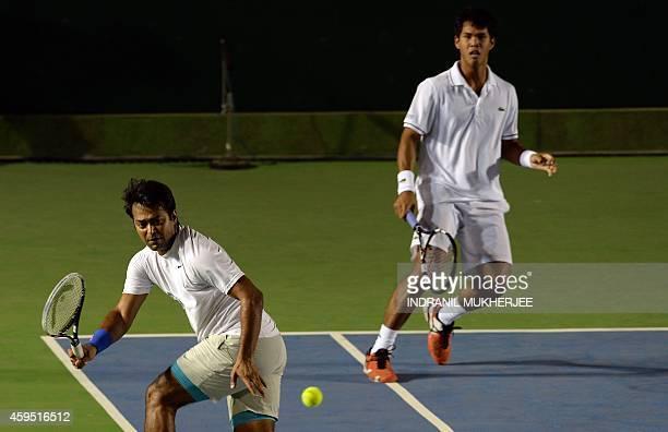 Punjab Marshals player Somdev Devvarman looks on as teammate Leander Paes plays a shot against Tommy Robredo and Sriram Balaji of Mumbai Tennis...