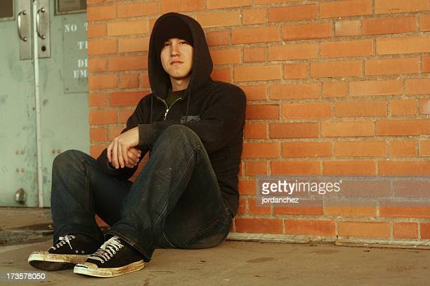Punk and a hoodie with dirty shoes sitting by brick wall