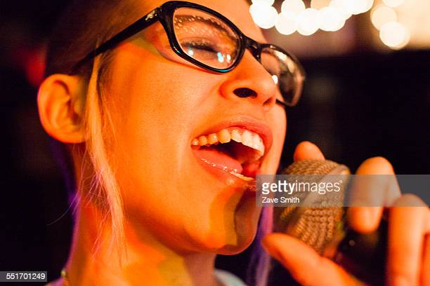 Punk girl singing into microphone, close-up