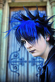 Goth Punk boy in front of gothic church door with blue and black hair
