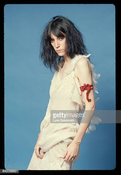Punk rock singer and poet Patti Smith poses for a studio portrait She wears feathers down her back meant to suggest an angel's wings and a red piece...