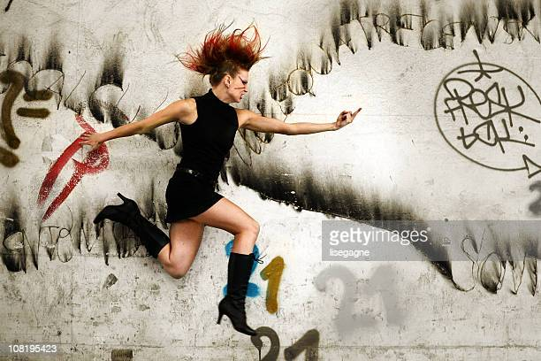 Punk Woman Jumping in Urban Area