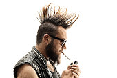 Punker lighting up a cigarette isolated on white background