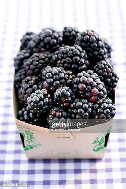 Punnet of blackberries on table cloth