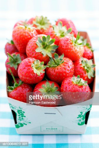 Punnet of strawberries on tablecloth