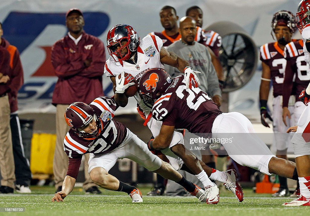 Punt return man Mason Robinson #24 of the Rutgers Scarlet Knights is tackled by Martin Scales #25 and A.J. Hughes #27 of the Virginia Tech Hokies during the Russell Athletic Bowl Game at the Florida Citrus Bowl on December 28, 2012 in Orlando, Florida.