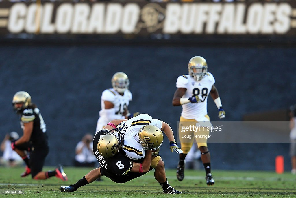 Punter Darragh O'Neill #8 of the Colorado Buffaloes tackles running back Steven Manfro #33 of the UCLA Bruins on a punt return at Folsom Field on September 29, 2012 in Boulder, Colorado. UCLA defeated Colorado 42-14.