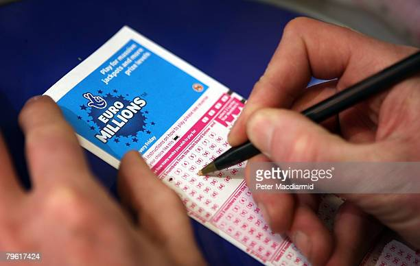 A punter fills out a National Lottery ticket on February 7 2008 in London A record breaking jackpot of 95 million is up for grabs in tomorrow's draw