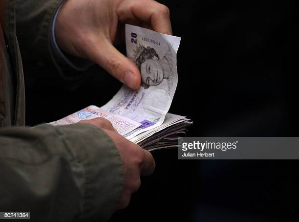 A punter hands over money for a bet at Cheltenham Racecourse on March 14 in Cheltenham England Today was the fourth day of The Annual National Hunt...