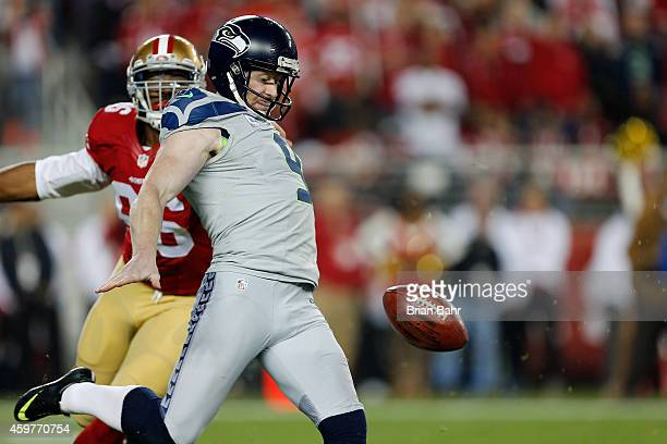 Punter Jon Ryan of the Seattle Seahawks gets off a 45yard kick after bobbling the ball and coming under pressure by linebacker Corey Lemonier of the...