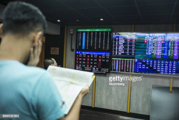 A punter reads a newspaper near a screen showing betting odds inside a betting hall at the Hong Kong Jockey Club's Happy Valley racecourse in Hong...