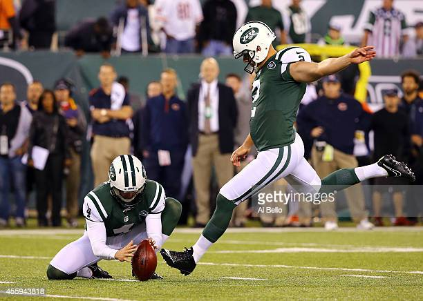 Punter Ryan Quigley holds the ball as kicker Nick Folk of the New York Jets hits a field goal against the Chicago Bears during a game at MetLife...