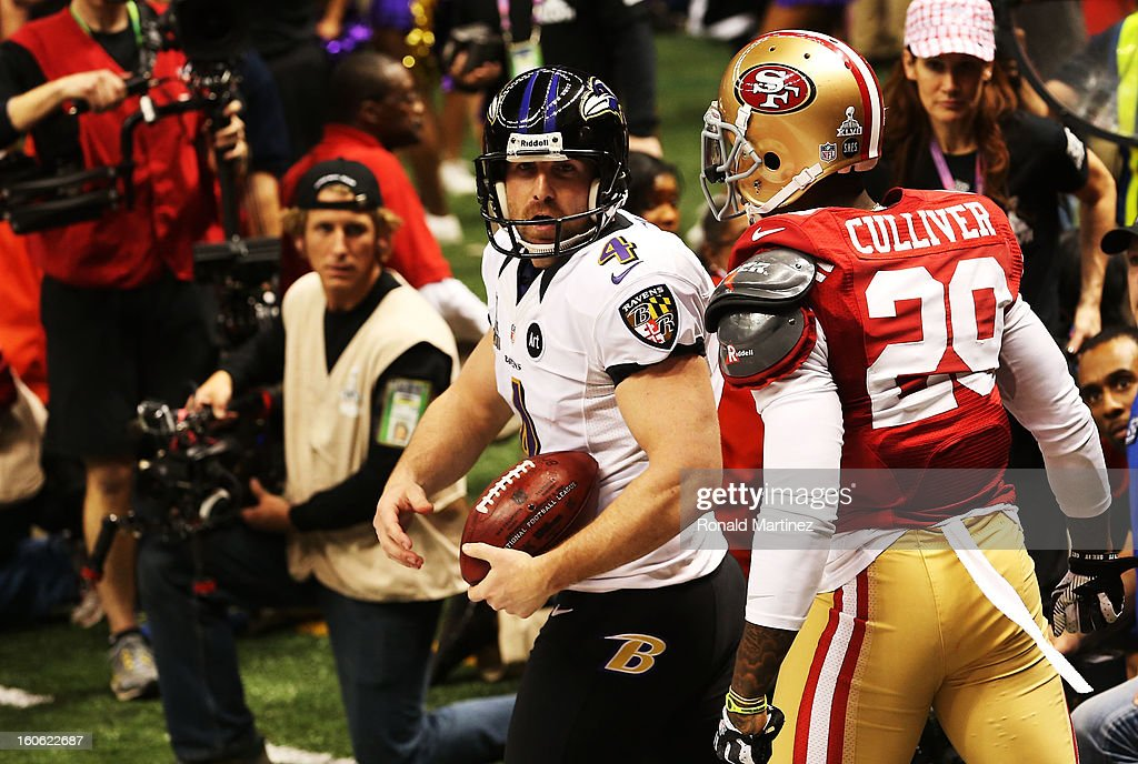 Punter Sam Koch #4 of the Baltimore Ravens holds the ball in the endzone as he takes a safety in the final minute of the fourth quarter against Chris Culliver #29 of the San Francisco 49ers during Super Bowl XLVII at the Mercedes-Benz Superdome on February 3, 2013 in New Orleans, Louisiana.