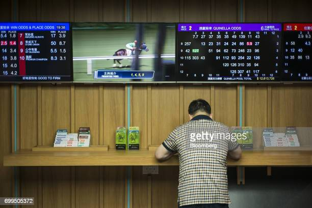 A punter stands near screens showing betting odds inside a betting hall at the Hong Kong Jockey Club's Happy Valley racecourse in Hong Kong China on...