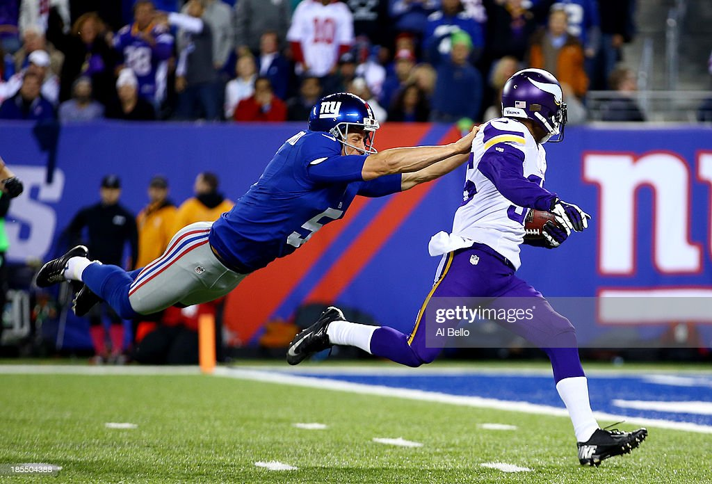 Punter Steve Weatherford #5 of the New York Giants tries to tackle cornerback Marcus Sherels #35 of the Minnesota Vikings as he returns a punt for a touchdown in the first quarter during a game at MetLife Stadium on October 21, 2013 in East Rutherford, New Jersey.