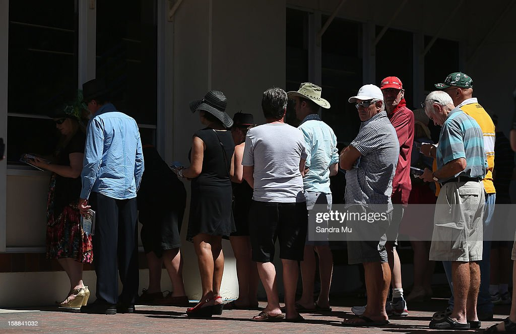 Punters line up at the tote to make a bet before The Sound Championship Stakes at Ellerslie Racecourse on January 1, 2013 in Auckland, New Zealand.