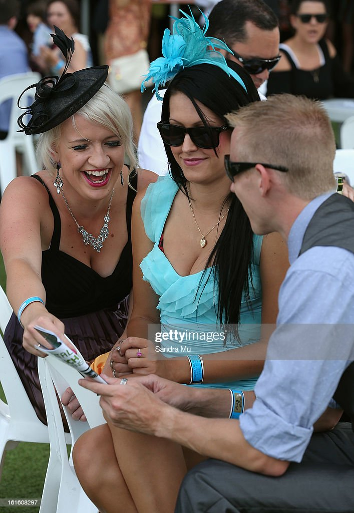 Punters look at the race book during the Auckland Twilight races at Ellerslie Racecoourse on February 13, 2013 in Auckland, New Zealand.