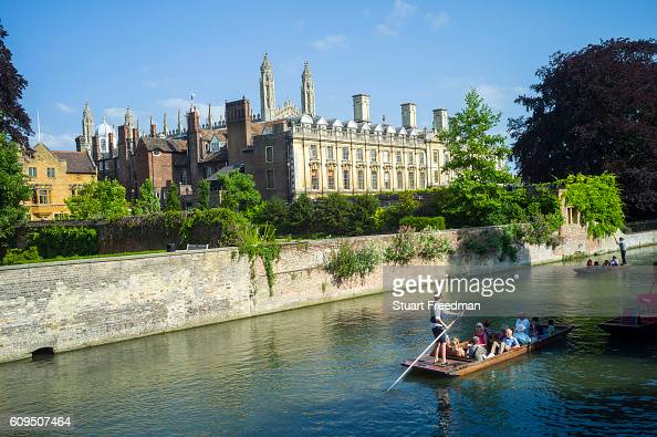 Punts and passengers glide past Clare College founded 1326 on the River Cam past the Garret Hostel bridge Cambridge UK