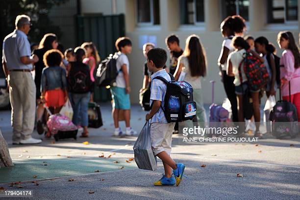 A pupil arrives in the courtyard of the Abbe de l'Epee elementary school on September 3 2013 in Marseille southern France prior to enter her...