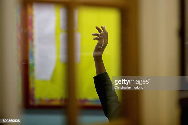 A pupil holds his hand up to answer a question in class at Altrincham Grammar School for Boys on September 8 2016 in Altrincham England The British...