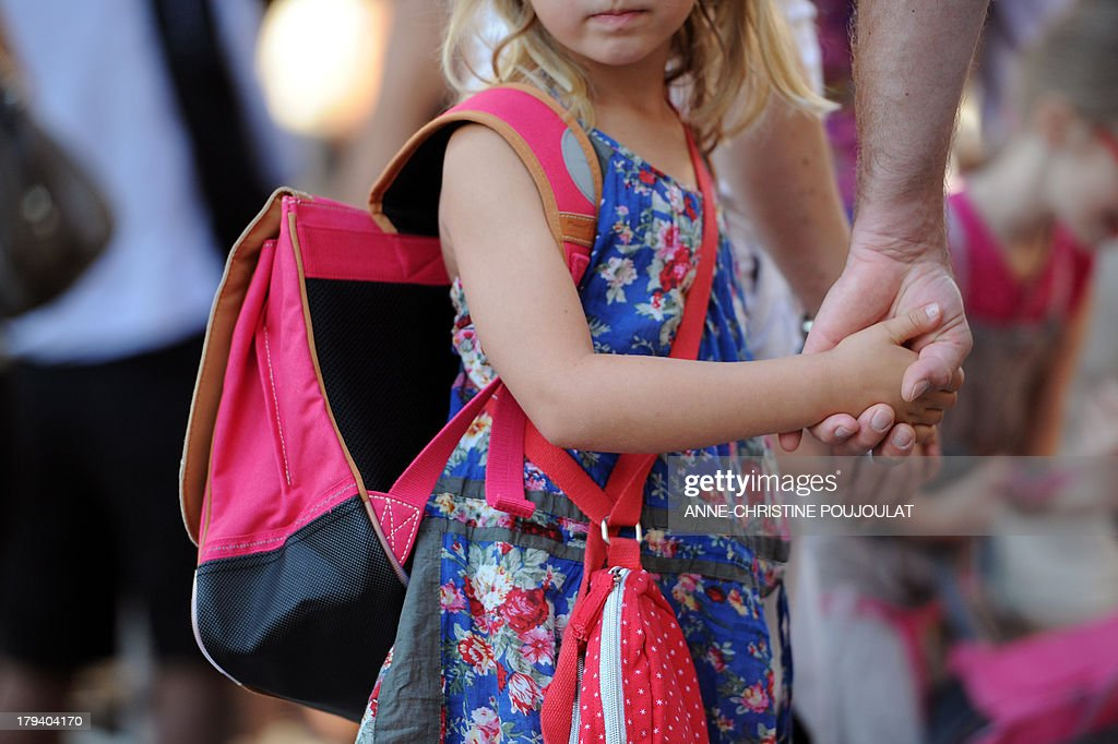 A pupil holds the hand of her father in the courtyard at the Abbe de l'Epee elementary school on September 3, 2013 in Marseille, southern France, prior to enter her classroom on the first day of school. More than 12 million pupils went back to school today in France.