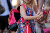 A pupil holds the hand of her father in the courtyard at the Abbe de l'Epee elementary school on September 3 2013 in Marseille southern France prior...