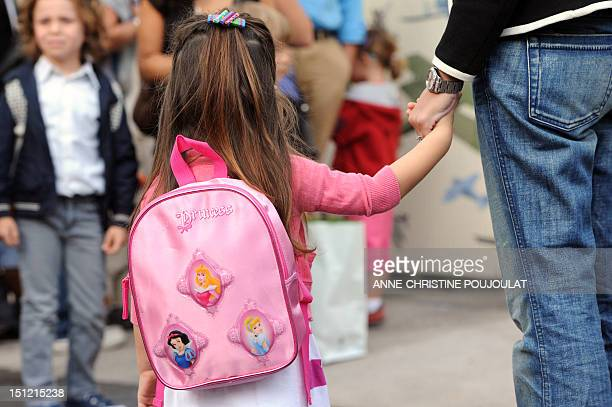 A pupil holds the hand of her mother in the courtyard of Jean Mermoz school on September 4 2012 prior enter in his classroom for an early start of...