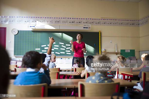 A pupil holds up an arm to ask a question to a teacher in a classroom at the elementary school on September 4 2012 in Paris after the start of the...
