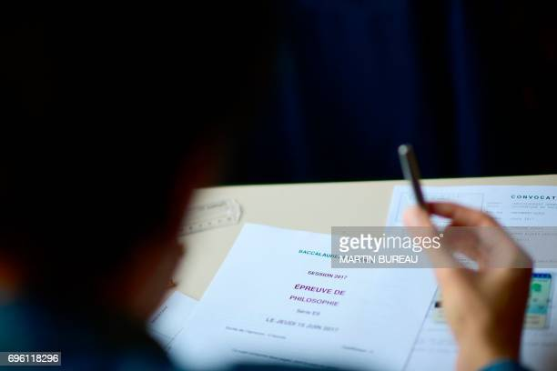 A pupil looks at the documents for the first written test in philosophy as part of the Baccalaureat at a school in Paris on June 15 2017 / AFP PHOTO...