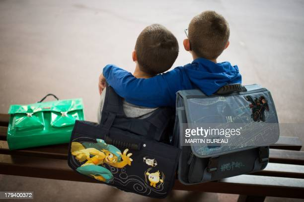 A pupil reassures a friend in the courtyard of a primary school on September 3 2013 in Paris on the first day of school More than 12 million pupils...