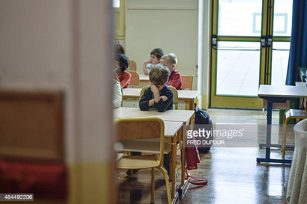 A pupil rubs his eyes in an elementary school on September 2 2014 in Paris after the start of the new school year AFP PHOTO / FRED DUFOUR