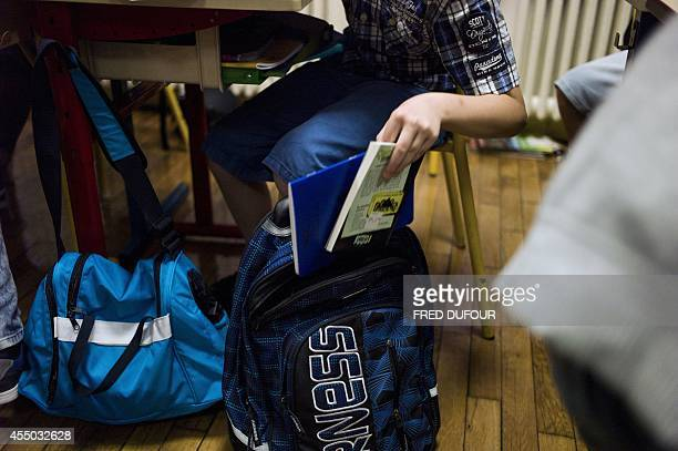 A pupil takes notebooks out of his schoolbag during a lesson at an elementary school on September 9 2014 in Paris AFP PHOTO / FRED DUFOUR