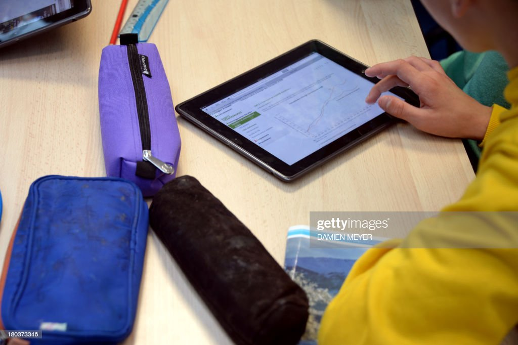 A pupil uses a tablet during courses in a classroom at the Leonard de Vinci 'connected' middle school in Saint-Brieuc, western France on September 12, 2013. The Leonard de Vinci school is one of the 23 middle schools in France to be connected to the internet and to be using new information technologies during courses.