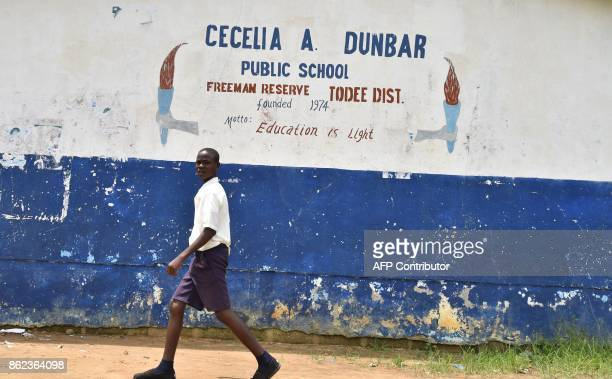 A pupil walks past outside the Cecelia Dunbar Public school in the city of Freeman Reserve in the Todee District about 30 miles north of Monrovia in...