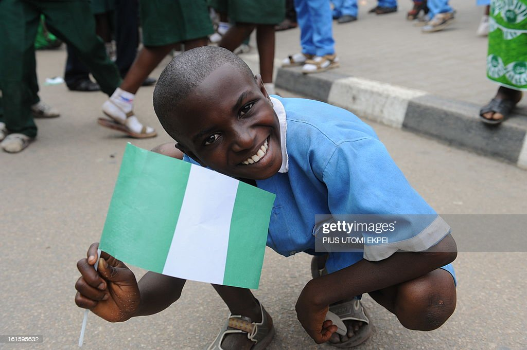 A pupil waves the Nigerian national flag to welcome the Nigerian football team at the airport in Abuja on February 12, 2013. The newly crowned African champions Nigerian Super Eagles arrives in Abuja to a warm reception by fans and government officials after defeating Burkina Faso to win the 2013 African Cup of Nations in South Africa. AFP PHOTO/PIUS UTOMI EKPEI