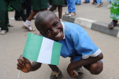 A pupil waves the Nigerian national flag to welcome the Nigerian football team at the airport in Abuja on February 12 2013 The newly crowned African...