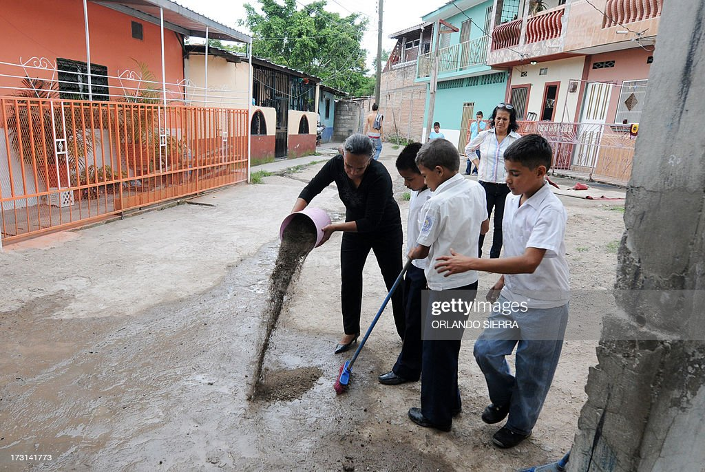 Pupils and teachers destroy a mosquito nest as part of a Health Ministry campaign focused on mosquito control in order to combat dengue fever, a disease caused by four strains of virus that are spread by the mosquito Aedes aegypti, in Tegucigalpa on July 8, 2013. Authorities have issued dengue alerts in four nations across Central America, where alarm is rising as the mosquito-borne disease has infected 30,000 people and killed 17 this year alone. The illness can be fatal, developing into hemorrhagic fever, which can lead to shock and internal bleeding. AFP PHOTO / Orlando SIERRA