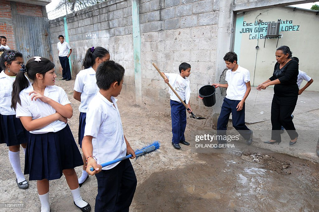 Pupils and teachers destroy mosquito nests as part of a Health Ministry campaign focused on mosquito control in order to combat dengue fever, a disease caused by four strains of virus that are spread by the mosquito Aedes aegypti, in Tegucigalpa on July 8, 2013. Authorities have issued dengue alerts in four nations across Central America, where alarm is rising as the mosquito-borne disease has infected 30,000 people and killed 17 this year alone. The illness can be fatal, developing into hemorrhagic fever, which can lead to shock and internal bleeding. AFP PHOTO / Orlando SIERRA