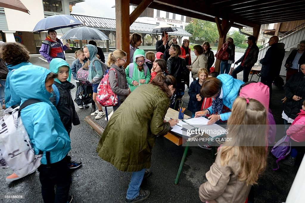 Pupils and their parents are welcomed by the staff of the elementary school 'Les Eterlous' on August 26, 2014 in Praz-sur-Arly, Haute-Savoie, on the first day of school, a week ahead of the official national start of the school year. Some 400 students of the mountain communities in Haute-Savoie returned to school on August 26, a week ahead of anyone else, under a waiver aimed to free every Wednesday morning during Winter for skiing.