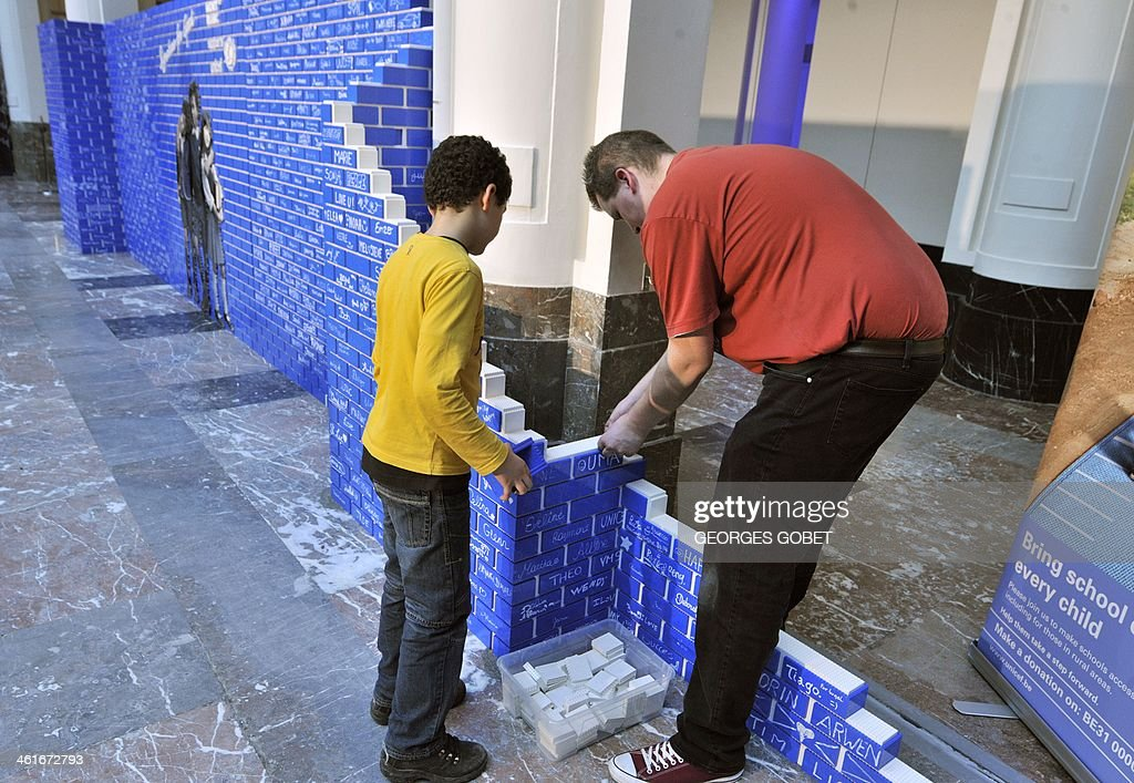 Pupils and volunteers help to build a record 20-meter-long wall made of 500,000 Lego blocks at the Palais des Beaux-Arts in Brussels (BOZAR) on January 10, 2014. The event takes place until Saturday to support the UNICEF campaign, which promotes the construction of schools in developing countries.