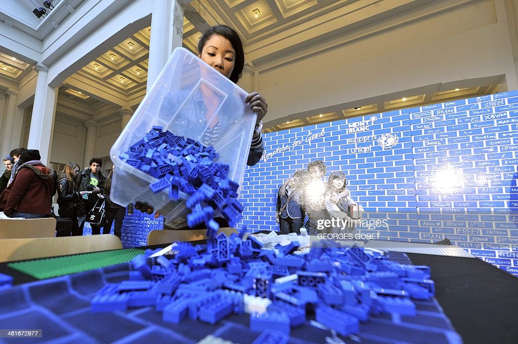 Pupils and volunteers help to build a record 20-meter-long wall made of 500,000 Lego blocks at the Palais des Beaux-Arts in Brussels (BOZAR) on January 10, 2014. The event takes place until Saturday to support the UNICEF campaign, which promotes the construction of schools in developing countries. AFP PHOTO / GEORGES GOBET