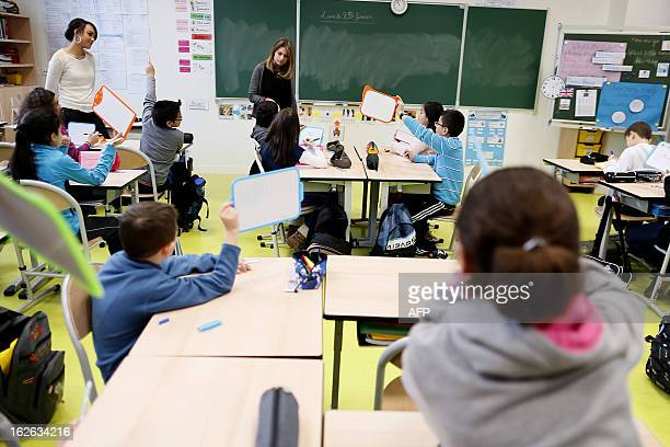 Pupils are pictured during a lesson on February 25 at an elementary school in Gonesse outside Paris AFP PHOTO KENZO TRIBOUILLARD
