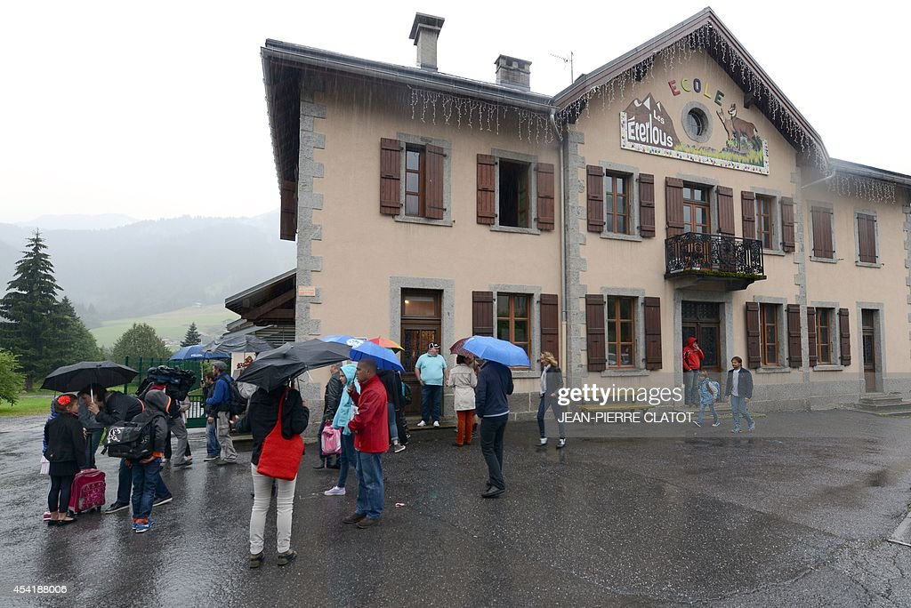 Pupils arrive with their parents at the elementary school 'Les Eterlous' on August 26, 2014 in Praz-sur-Arly, Haute-Savoie, on the first day of school, a week ahead of the official national start of the school year. Some 400 students of the mountain communities in Haute-Savoie returned to school on August 26, a week ahead of anyone else, under a waiver aimed to free every Wednesday morning during Winter for skiing.