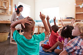 Pupils At Montessori School Raising Hands To Answer Question