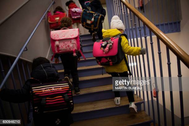 Pupils climb stairs as they arrive for a class following the Freinet teaching method on December 12 2016 in Paris The Freinet teaching method...