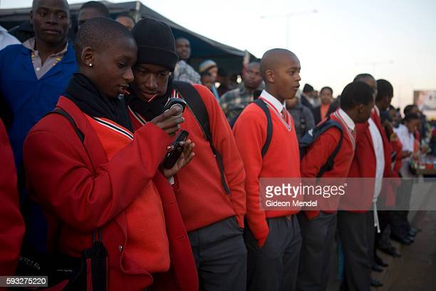 Pupils compare their mobile phones as they queue for transport at the Baragwanath taxi rank which will take them to their school outside of Soweto...
