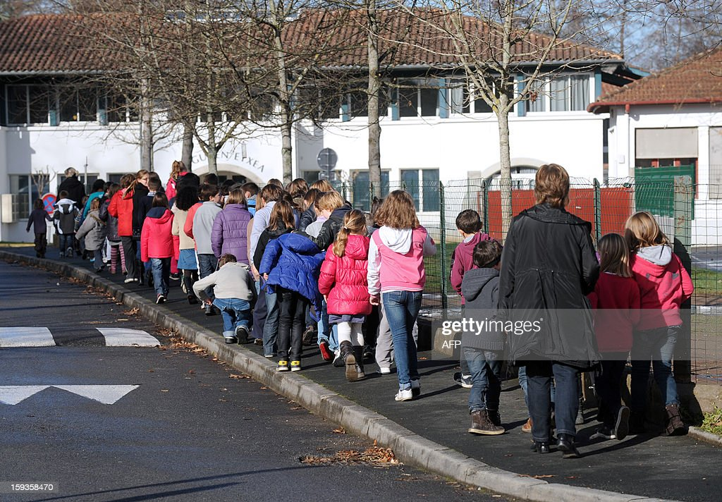 Pupils from the Saint-Vincent private school walk along the sidewalk on January 11, 2013 in Ustaritz, southwestern France. A municipal policewoman expelled on January 9 a five-year old pupil from the municipal canteen, for unpaid 170 euros, at the request of the mayor.