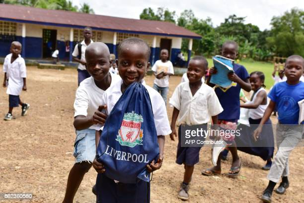 Pupils gather and play outside the Cecelia Dunbar Public school in the city of Freeman Reserve in the Todee District about 30 miles north of Monrovia...