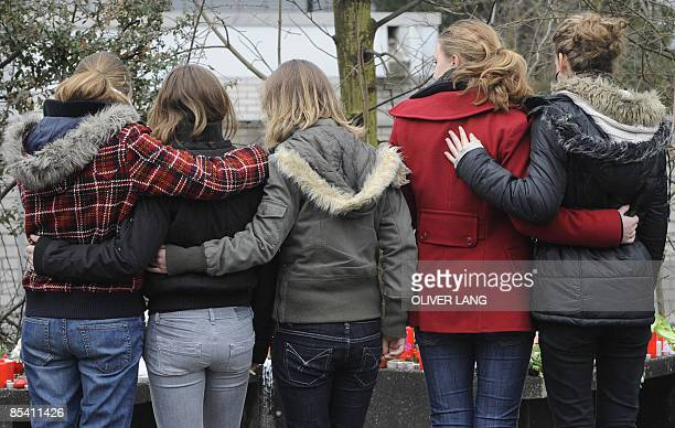 Pupils mourn next to a sea of flowers and candles left by residents in front of the Albertville secondary school on March 13 2009 in Winnenden...