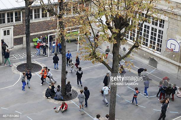Pupils play on a school playground at the Ampere primary school of Paris on October 13 2014 AFP PHOTO /THOMAS SAMSON
